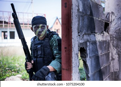 Special forces soldier  or private millitary holding gun behind concrete obstacle.
