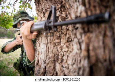 Special forces soldier  or private millitary holding gun aiming behind a tree at field area.