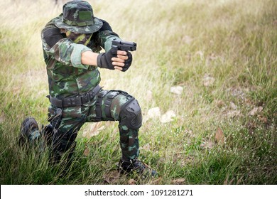 Special forces soldier  or private millitary sit holding gun aiming.