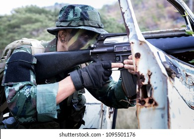 Special forces soldier  or private millitary holding gun aiming behind a dilapibated car at field area.