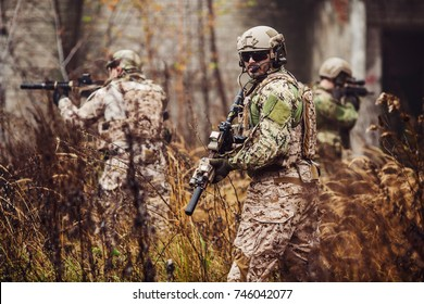 Special forces soldier with rifle in full gear. Military man on the background of nature.