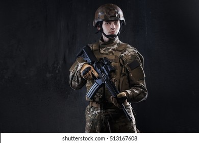 Special forces soldier with rifle on dark background. Ammunition Soldier.