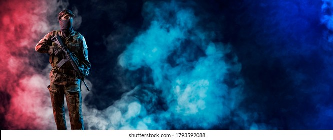 Special forces Soldier of  standing in the smoke.  Infantryman fighting with terrorism. Commando on smoky red and blue light background with rifle.