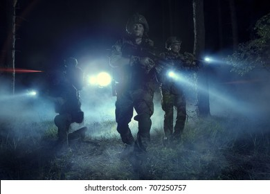 Special Forces soldiers in action. Elite squad moves through fog and smoke. They use special equipment, weapons and tactical devices.