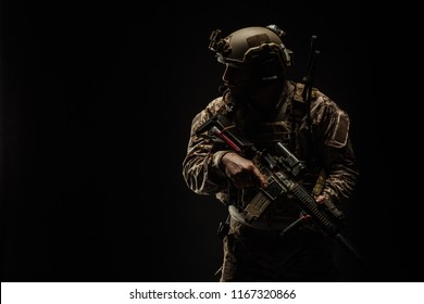 Special forces United States soldier or private military contractor holding rifle. Image on a black background. war, army and weapon concept