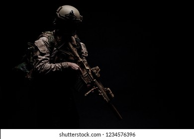 Special forces United States soldier or private military contractor holding rifle. Image on a black background. war, army, weapon, technology and people concept