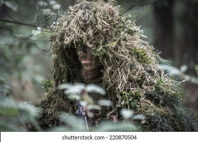 special forces warrior wearing heavy camouflage, moving silently through forest.