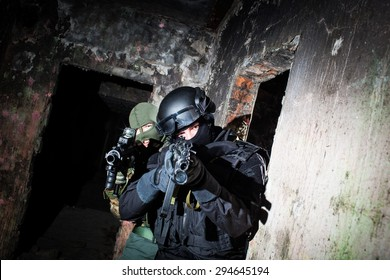 Special forces/anti-terrorist unit or contractor team during night CQB mission/operation (color toned image, very harsh lighting is used on this shot to underline the atmosphere of night mission)