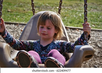 Special needs child with autism enjoying her chair swing on a spring day