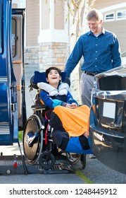Special needs eleven year old boy in wheelchair outdoors ready to ride on the vehicle wheelchair lift with father