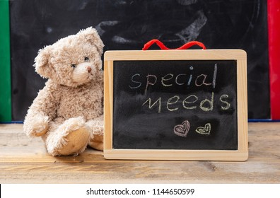 Special needs at school. Teddy bear hiding behind a blackboard. Special needs text drawing on the blackboard