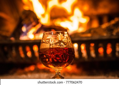 Special occasion alcohol drink in single chrystal glass agains fireplace with burning fire and warm flame.