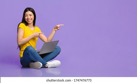 Special Offer. Cheerful asian girl sitting on floor with laptop and pointing at copy space over purple background, panorama