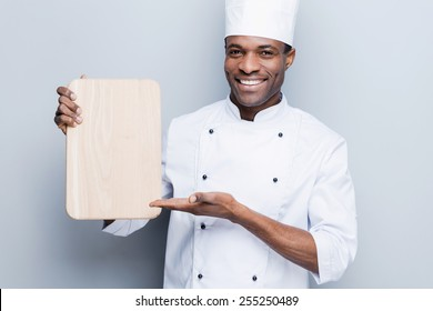 Special offer from chef. Confident young African chef in white uniform holding wooden cutting board and pointing it with smile while standing against grey background