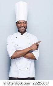 Special offer from chef. Confident young African chef in white uniform pointing away and smiling while standing against grey background