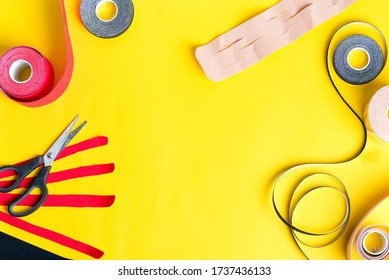 Special physio tapes rolling of different colors and scissors for cutting on a yellow background. Kinesiology taping treatment.