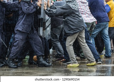 Special police unit with shields against protesters,Protester Pushes Police Riot Shields at a Political Rally.