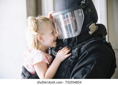 special policeman holding a little girl in his arms