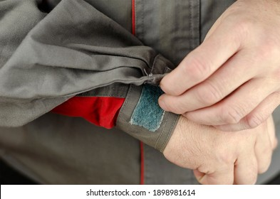 Special protective clothing for work. Man's hands are fastened with hook-and-loop clip on the sleeve of gray work jacket with red inserts. Close-up, selective focus. - Shutterstock ID 1898981614