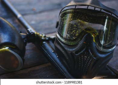 Special protective mask for playing paintball with traces and spot of hit of a ball with paint. Equipment for playing paintball on a wooden table. Game marker and a protective mask. Image photography.