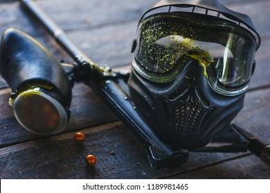 Spezielle Schutzmaske für Paintball mit Spuren und Fleck eines Balles mit Farbe. Ausrüstung zum Spielen von Paintball auf einem Holztisch. Spielmarke und Schutzmaske. Bildfotografie.