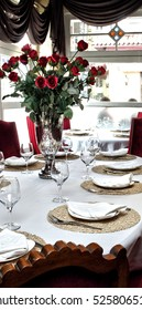 Special service plates, glasses, vases and roses. Set a table