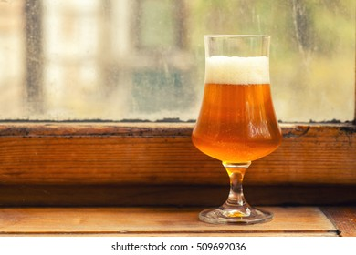 Special snifter glass full of strong amber ale on a wood windowsill