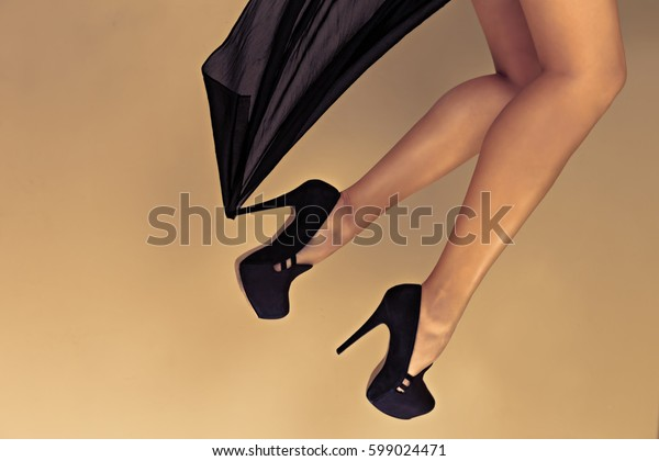 Special toned photo of female legs in black silk fabric and in high heels shoes lying on floor, horizontal view