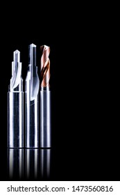 Special tools isolated on dark background. Made to order special tools. Coated step drill and reamer detail. HSS cemented carbide. Carbide cutting tool for industrial applications. Engineering tools.