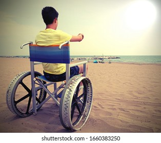 special wheelchair with big wheels in aluminium and a boy in summer with old toned effect