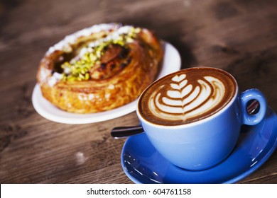 Specialist coffee shop A cup of coffee with a fern leaf pattern in the froth, and a croissant on a plate