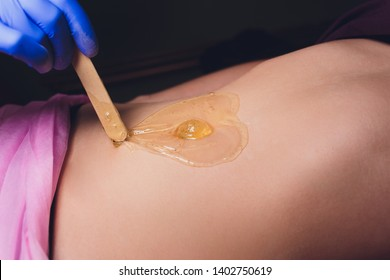 specialist cosmetologist professional removes unwanted hairs from female client's body.shugaring of legs and bikini area in the spa salon honey and sugar.