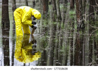 specialist in coveralls taking sample of water to container in floods contaminated area
