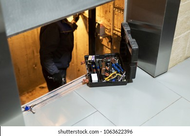 Specialist fixing or adjusting lift mechanism in elevator schaft. Regular repair, service and maintenance of elevator