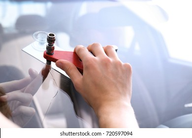 Specialist fixing crack on car windshield in repair shop