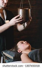 Specialist making shirodhara massage form of ayurveda therapy. beautiful woman spending time at modern spa cabinet relaxing. Soft yellow light