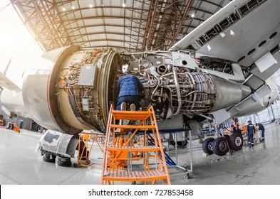 Specialist mechanic repairs the maintenance of a large engine of a passenger aircraft in a hangar