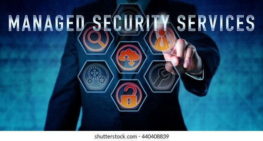 IT specialist is pressing MANAGED SECURITY SERVICES on an interactive virtual touch screen interface. Business metaphor and computer network security concept for outsourced MSS customer care.