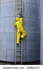 specialist in protective uniform going up a metal ladder on storage tank