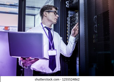 IT specialist. Serious handsome man holding his laptop while checking wires