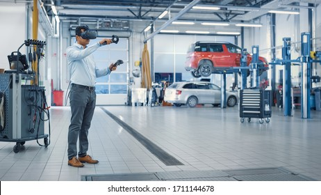 Specialist is Wearing a Virtual Reality Headset and Holding Two Joysticks in a Car Service. Mechanic is Investigating the Breakdown with the Help of Future Technology. Repairman in Modern Workshop.