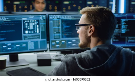 IT Specialist Working on Personal Computer with Monitors Showing Coding Language Program. Technical Room of Data Center.