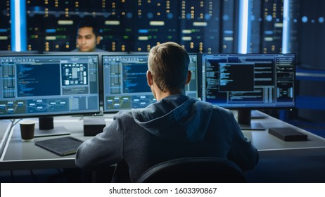 IT Specialist Works on Personal Computer with Screens Showing Software Program with Coding Language Interface. In the Background Technical Room of Data Center with Professional Working