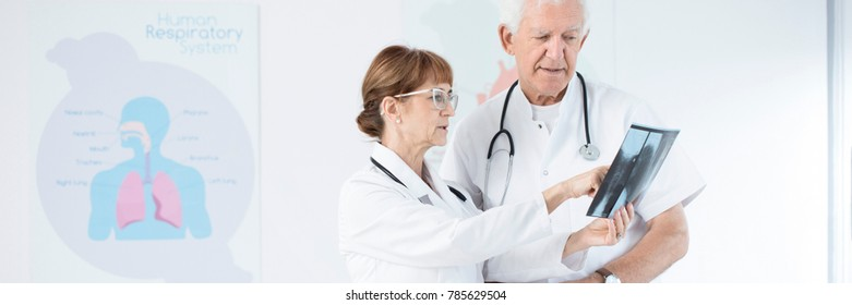 Specialists in white uniforms consulting X-ray photo in a hospital