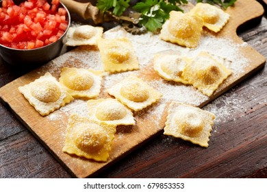 Speciality handmade uncooked Italian ravioli pasta with spicy salsa and parsley on a rustic wooden floured board in a close up view