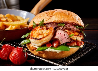 Speciality Surf and Turf burger with scampi and roasted beef with rocket, petit pois and tomato on a wire rack with a side serving of French Fries