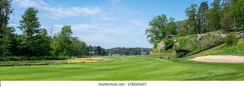 "Specially trimmed meadows with green upper golf ball court ""Tee"" for playing. Stairs up. Panoramic view of Golf course with holes, sand bunker and pond. Few players due to coronavirus. Header. Banner."