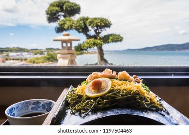 A specialty of Yamaguchi, Japan, kawara soba features green tea soba crisped on a hot roof tile topped with meat, shrimp, eggs, and seaweed, to be dipped in broth; traditional Japanese view behind