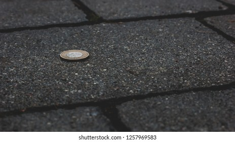 Specie lying on dark paving, money is on the street, lost small change
