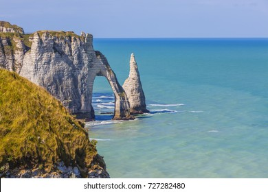 Specific cliffs in Etretat in the Upper-Normandy region in Northern France at low tide: the needle rock and the stone arch.